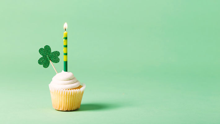 Cupcake with green candle and clover decoration on a green background