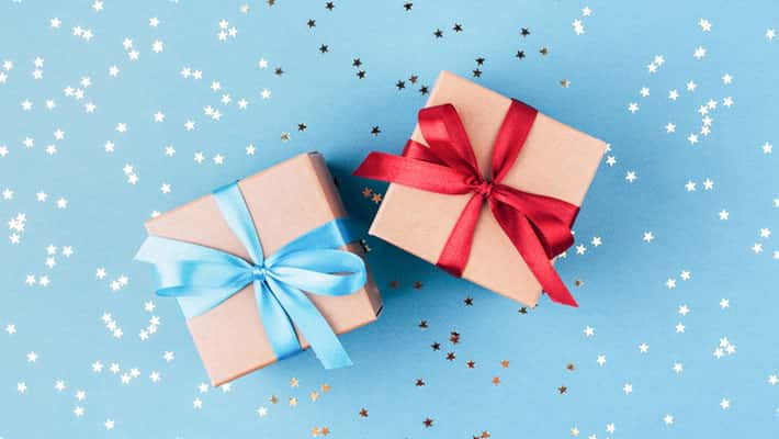 Two gift boxes wrapped in kraft paper and tied with ribbon on blue background decorated with confetti