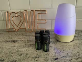 bottles of essential oils in front of a diffuser and love sign