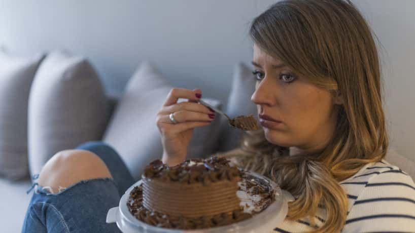 Sad woman eating chocolate cake