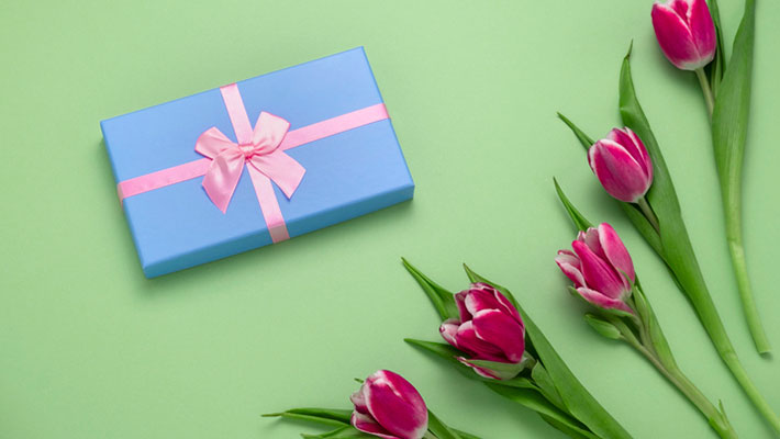 Blue gift box with pink bow and tulips on a green background