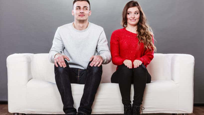 Shy man and woman sitting next to each other on a couch