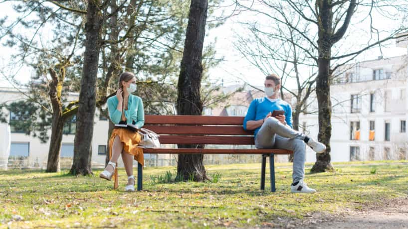 Woman and man with face mask in social distancing sitting on a park bench