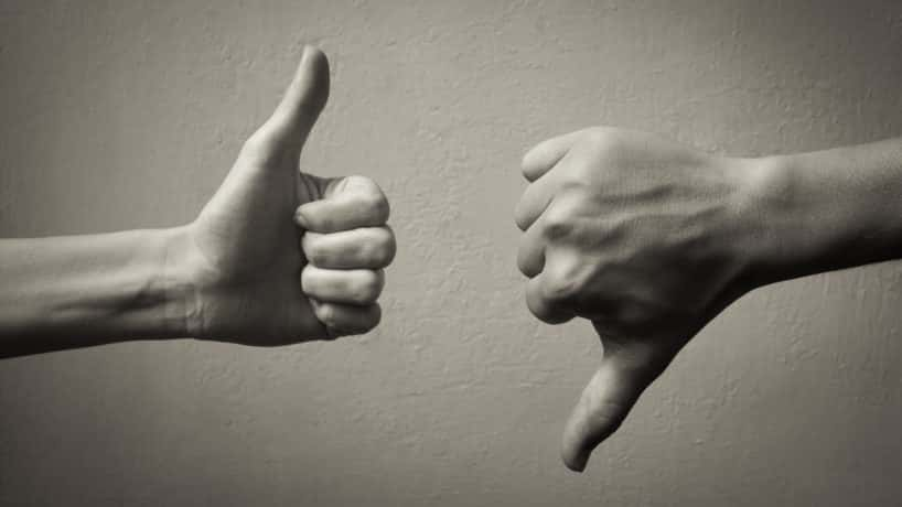 Photo of one hand with thumb up and an opposing hand with a thumb down