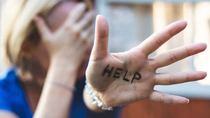 "Woman gesturing ""help"" sign on her hand."