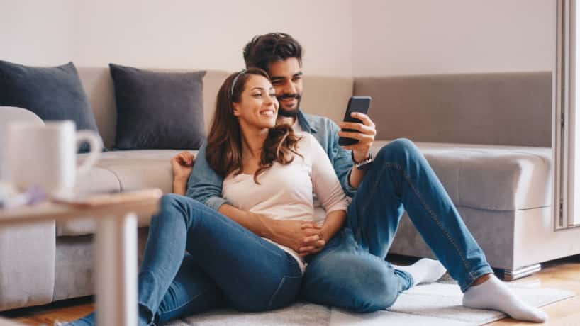 couple sitting together looking at mobile phone