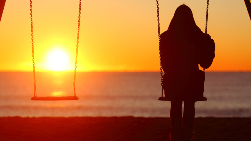 Single woman sitting on a swing contemplating sunset