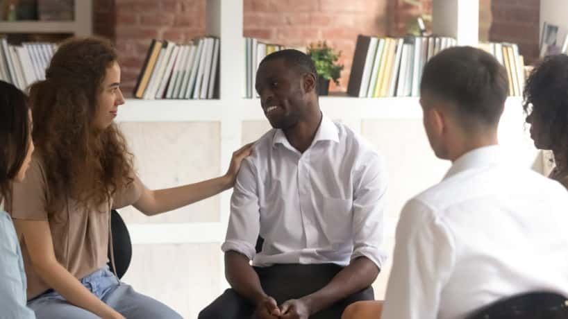 Supportive woman placing hand on the shoulder of a man in a support group