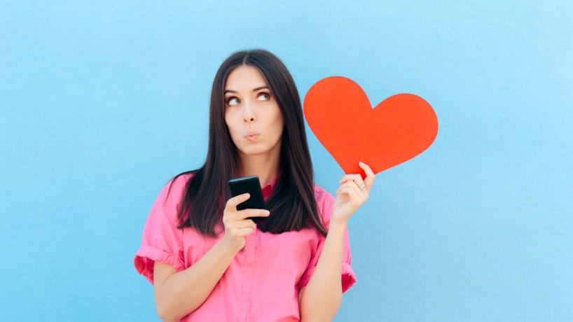 Girl using dating app on her phone while holding a red heart