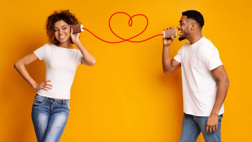 African-american man singing love song to his girlfriend via tin phone, orange studio background