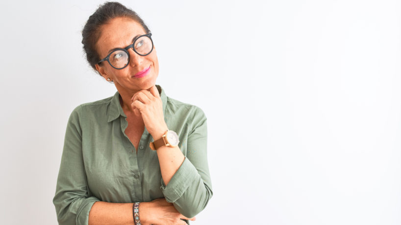 Middle age woman wearing green shirt and glasses standing over isolated white background with hand on chin thinking about question, pensive expression. Smiling with thoughtful face. Doubt concept. - stock photo