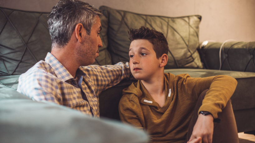 Dad talking to teen son on the couch.