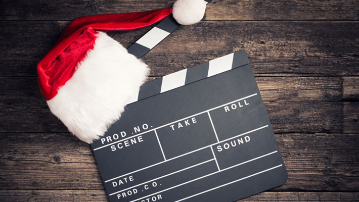 Santa hat on a clapperboard on a wood background