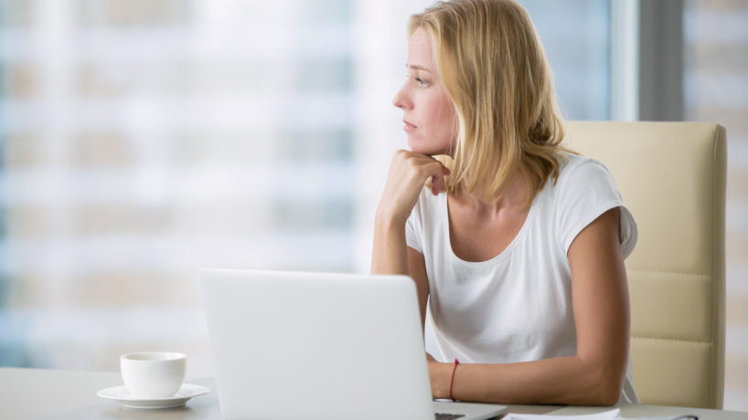Young attractive woman at a modern office desk, working with laptop, looking at the window, thinking about a post, full-time blogger, seeking for inspiration, help to be productive, updating computer