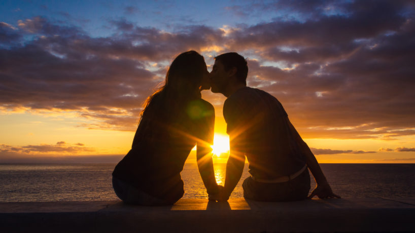 Couple silhouette enjoying romantic colorful twilight. Valentines Day, honeymoon romantic date concepts
