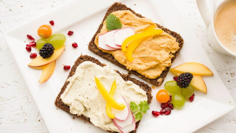 pieces of bread with spread on them and a fruit and coffee on the side.