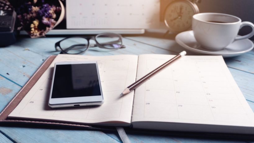 Diary Calendar and agenda for Planner to plan timetable,appointment,organization at office. Desktop Calender 2020,smartphone,clock,book and cup of coffee place on desk,work from home.Calendar Background Concept