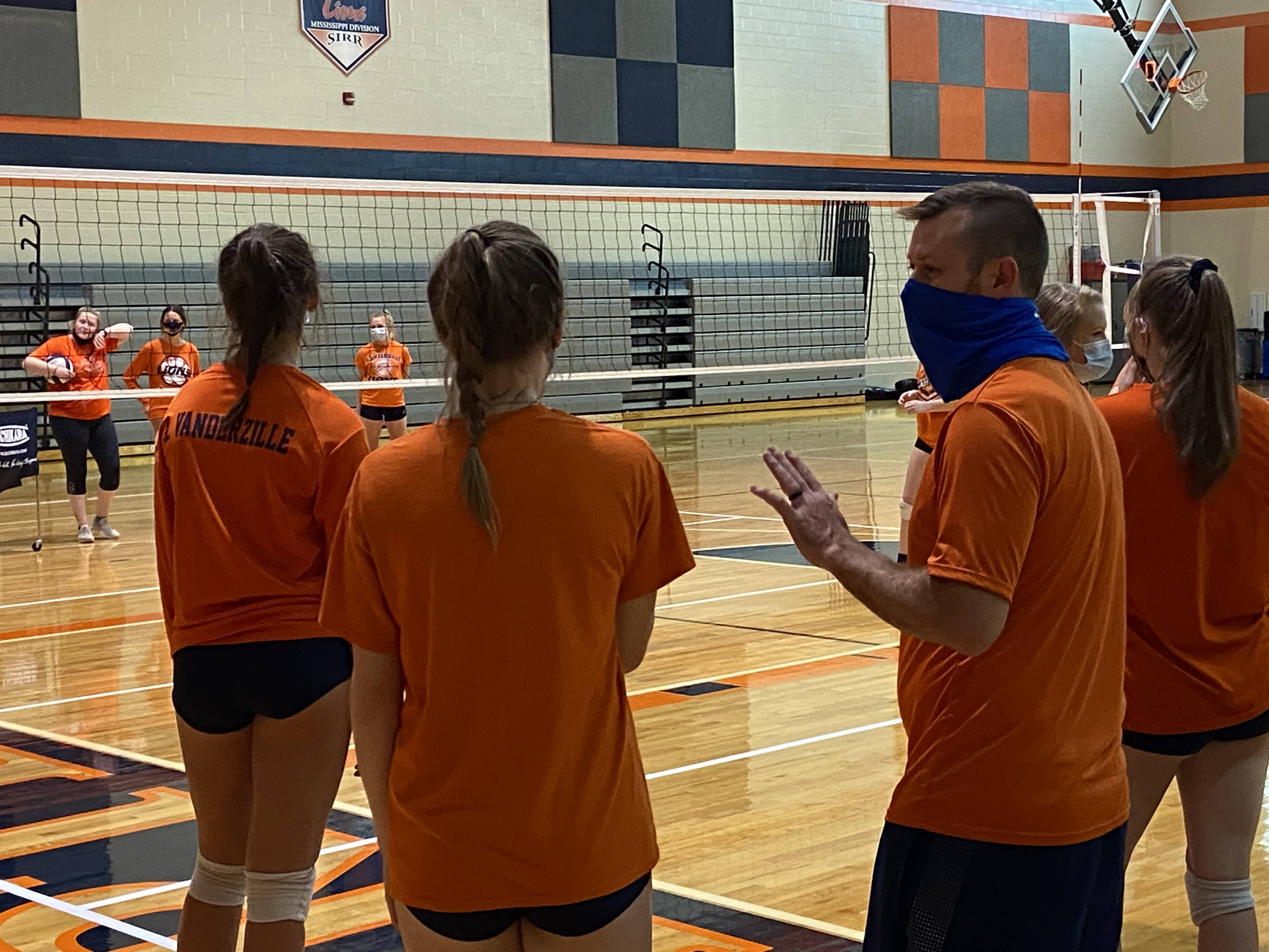 Carterville Volleyball coach Nathan Emrick instructs his players in a contact day practice in October 2020