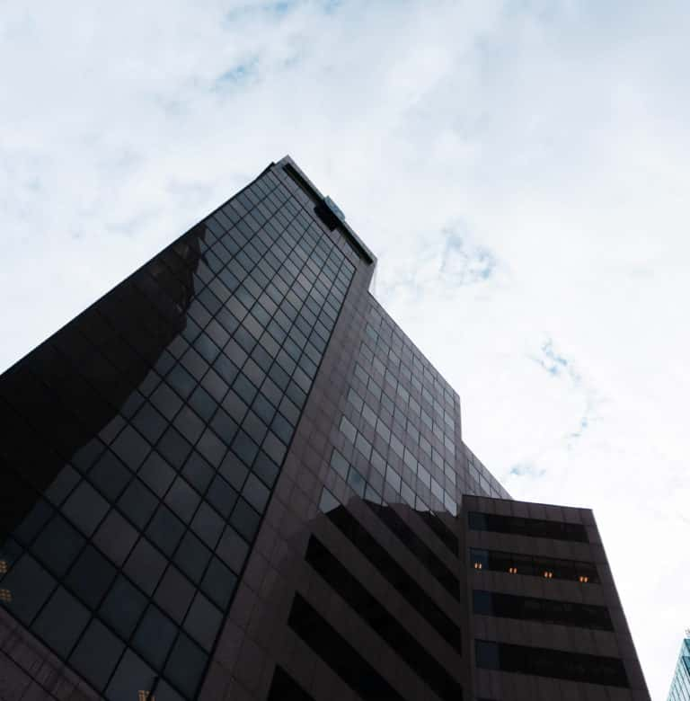 Downtown indianapolis office building from a lower angle with blue sky and clouds in the background