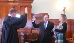 District Court Judge William Ostlund (left) swearing in County Attorney Thomas Laehn (middle) as his wife Susan and daughter Sophia (right) look on