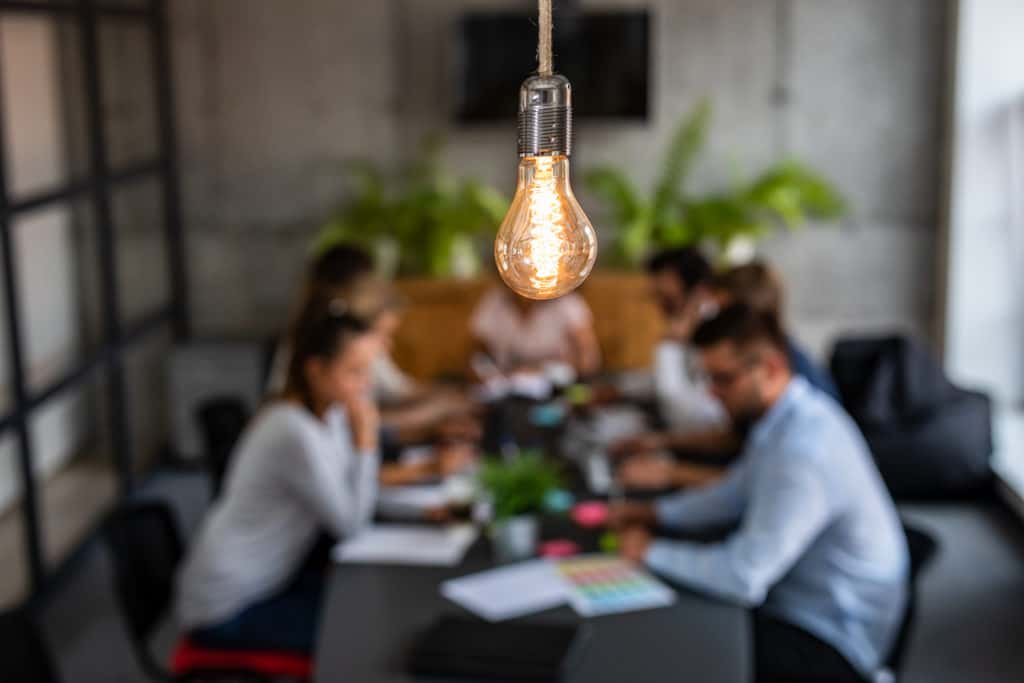 hanging lit lightbulb with blurred background of 5 people sitting around a conference room table with scattered papers on the table