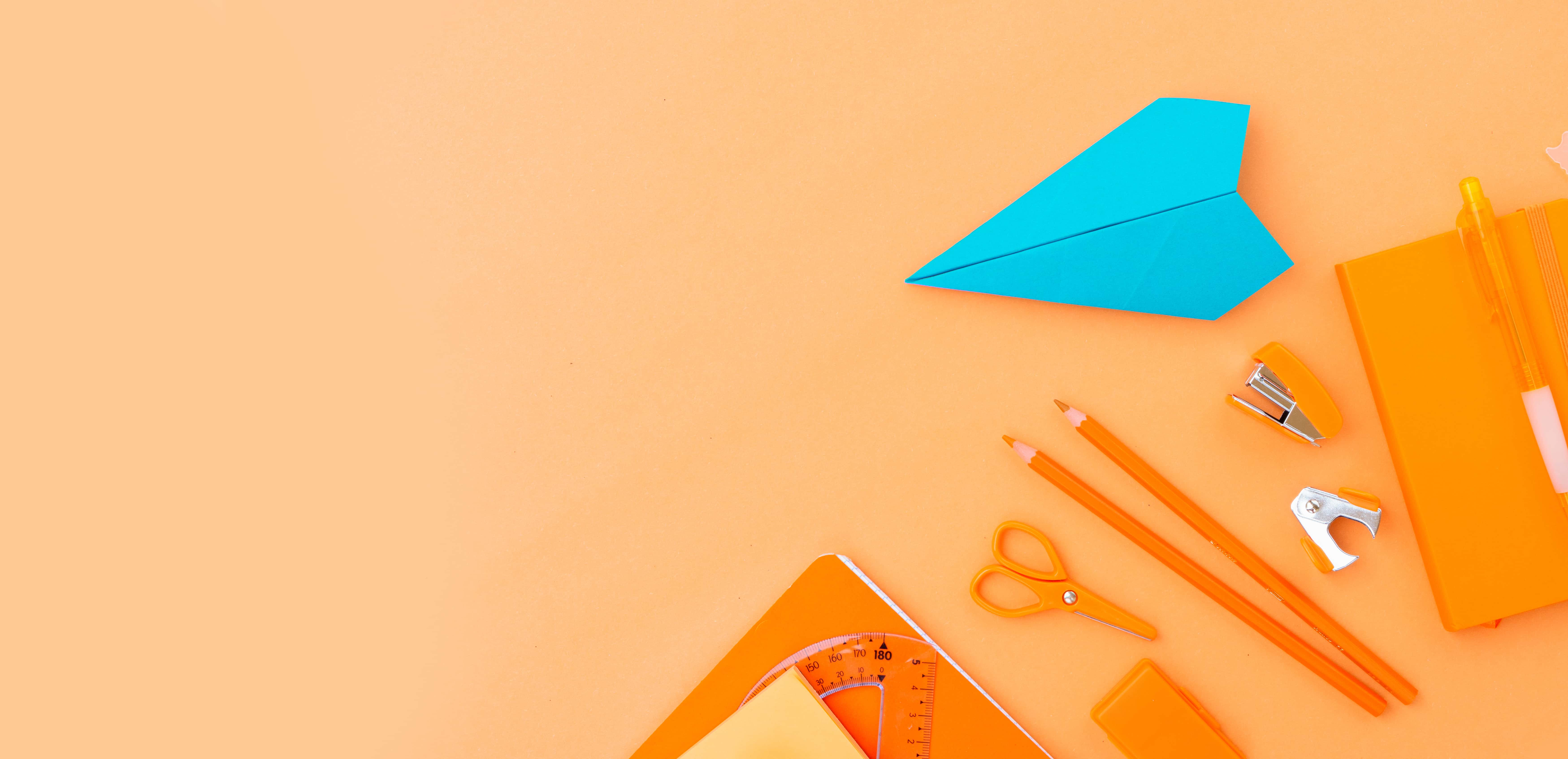 orange background with orange office supplies and turquoise paper airplane