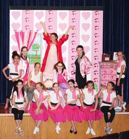 """Marty, played by CMS seventh grader, Stella Santini, belts out """"Freddy My Love"""" during a Central Middle School rehearsal of Grease. Marty shown centered, with Rizzo (standing to the right played by Lea Bain) and Sandy, (seated on the left and played by Isobelle Novak) surrounded by the Pink Ladies and Pinkettes."""