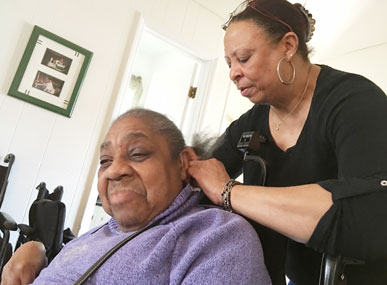 Trovetti Griffin braids a resident's hair in an Old Greenwich home which is managed by Abilis. Griffin has worked in the Abilis residential program for eight years. [Contributed photo]