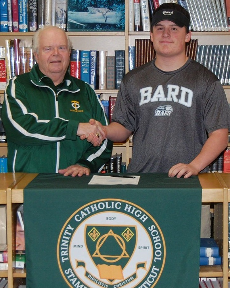 Trinity Catholic High School Athletic Director and Head Baseball Coach Tracy Nichols congratulates senior Dillon Daine after he signed his National Letter of Intent to play baseball at Bard College (Contributed Photo)