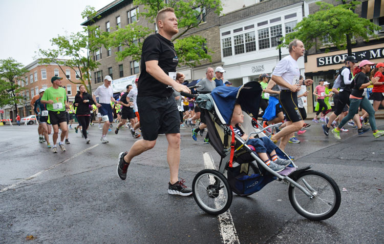 Port Chester resident Chris Budden races, with child in tow, during the Memorial Day Jim Fixx Road Race in Greenwich. (photo courtesy of Michael Yardis / Threads and Treads)