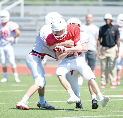 Members of the white team apply the tackle during Saturday's scrimmage. (John Ferris Robben photo)