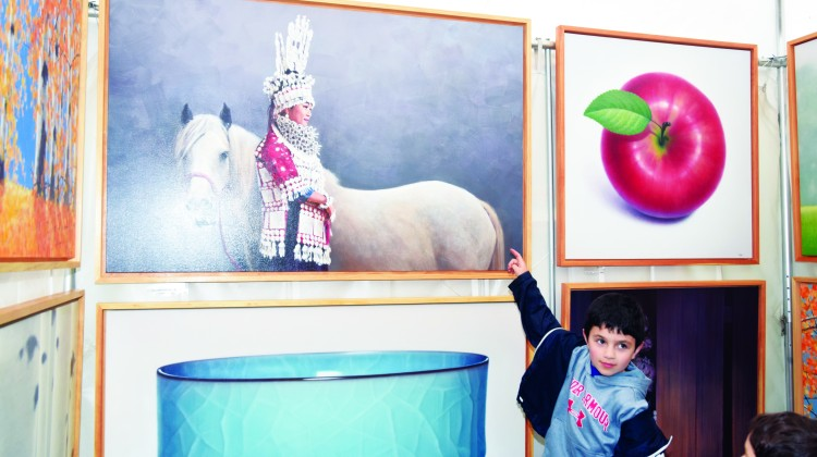 Misha Shteingart, 8 years old, points to his favorite painting at the Bruce Museum Outdoor Festival. Photo by Chèye Roberson