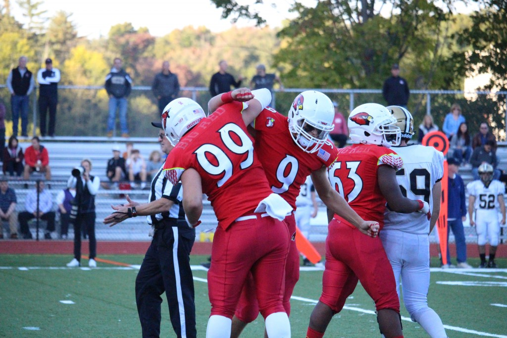 Greenwich's Sam Colandro and Ian Pearson celebrate after recording a sack against Trumbull in Saturday's 42-32 win (Evan Triantafilidis photo)