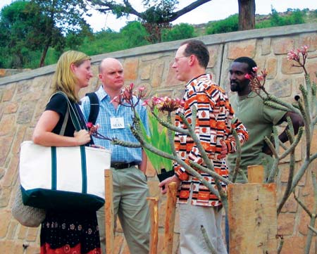 Lesley King in the field in Rwanda, talking of the Rwinkwavu Hospital expansion with Partners in Health co-founder Dr. Paul Farmer, on right, and Trinity Church member Sean Cassidy, and, right rear, Bruce Nizeye, head of construction for Partners in Health in Rwanda. (contributed photo)