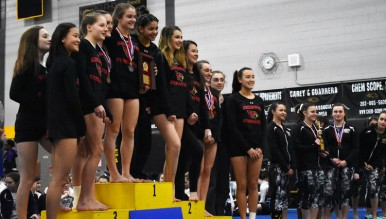 After claiming its first FCIAC title since 1982 last season, the Greenwich High School gymnastics team celebrates winning back-to-back FCIAC championships Saturday afternoon at Jonathan Law High School in Milford. (Paul Silverfarb photo)