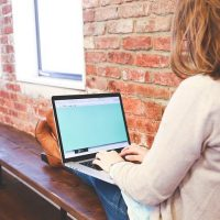 Woman accessing internet on laptop near brick wall