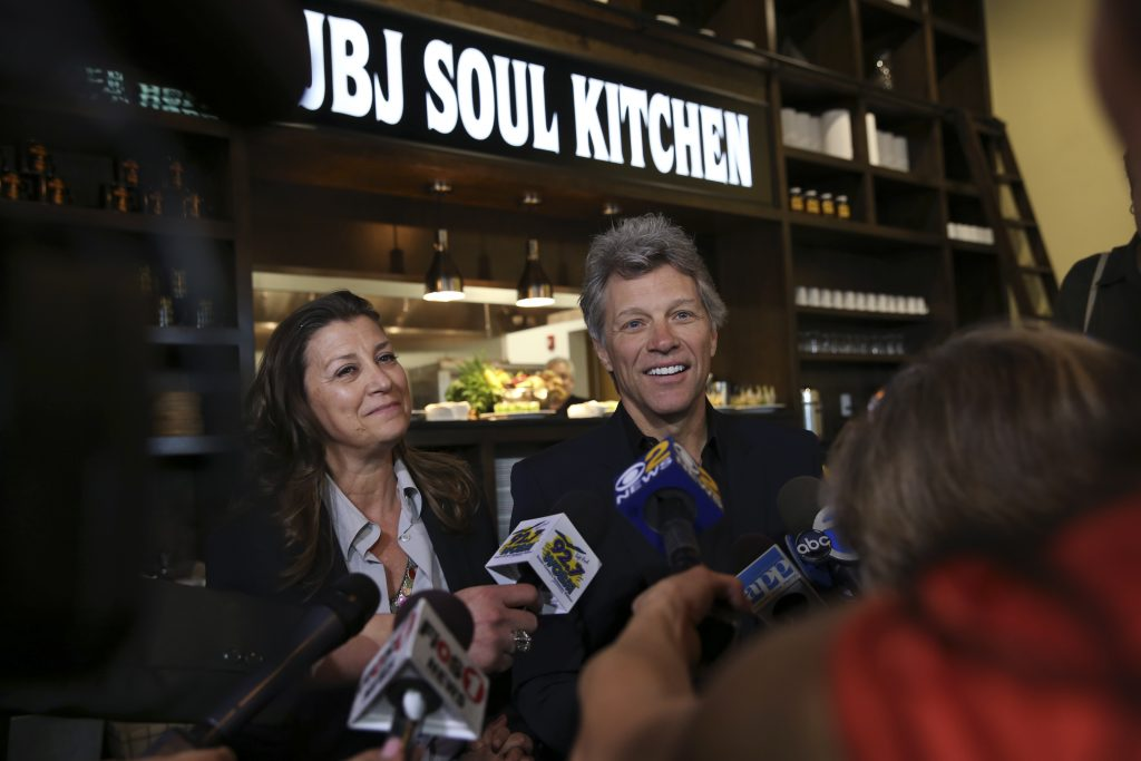 rock star and philanthropist jon bon jovi listens to a question as he stands with his wife dorothea hurley in jon bon jovi soul foundations soul kitchen - Jon Bon Jovi Soul Kitchen