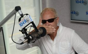 Dana Crypto in north shore 1049 studio with sunglasses on and hand over mouth