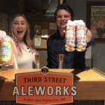 Amber and Tanner proudly holding their own beers made in collaboration with their friends at Third Street Aleworks.