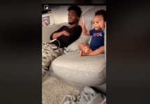 dad chats with his baby while watching tv