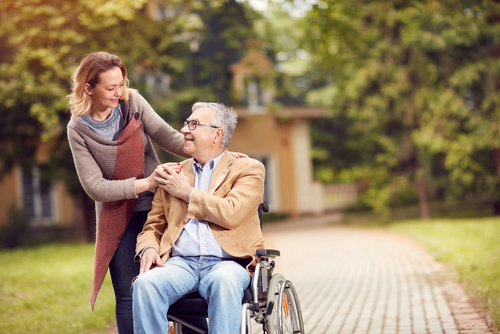 A woman and an elderly man shopwcasing patient-centered care in the park.
