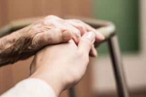 Image of an elderly person's hand touching a younger nurse's hand.