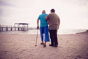 Man assisting elderly man with walking on the beach, an example of patient-centered care.