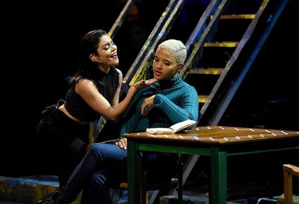Vanessa Hudgens as Maureen Johnson sings to Kiersey Clemons as Joanne Jefferson. Joanne is sitting at a desk and looking somber