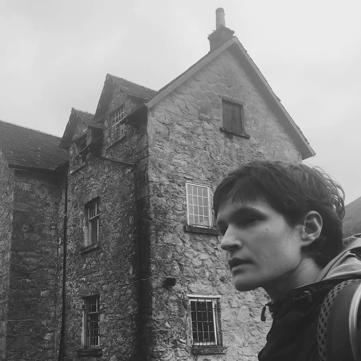 Black and white photo of Adrianne in front of an old stone house