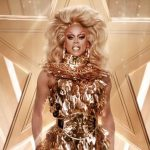RuPaul in drag on stage wearing all gold