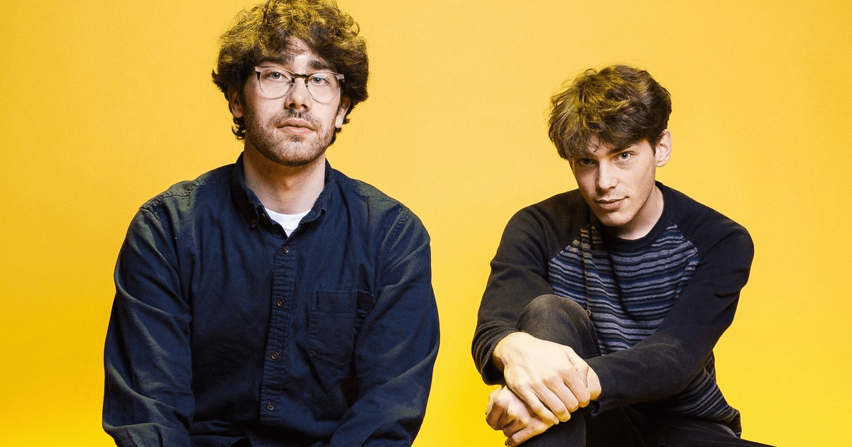 Stephen and Erik Paulson sit in front of a yellow background, looking at the camera