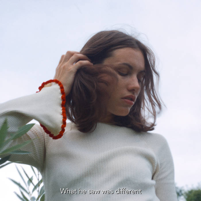 Girl with brown hair in a white shirt turns her head to the side, away from the camera