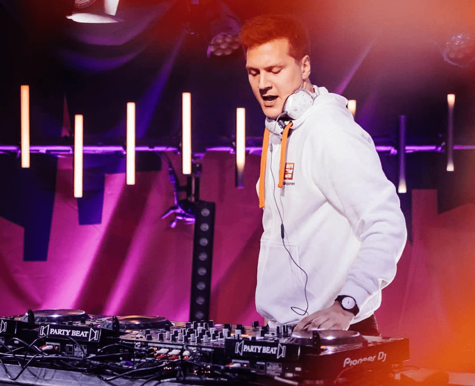 Matoma mixing beats on a mixing table, wearing a white hoodie, illuminated by pink and orange lights.