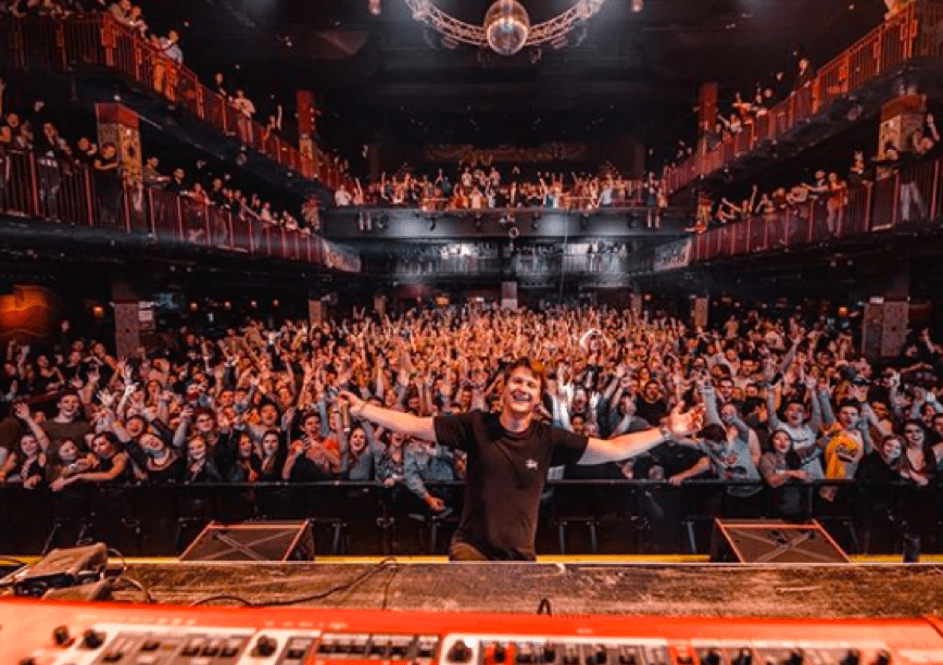 Matoma smiling in front of a large audience.